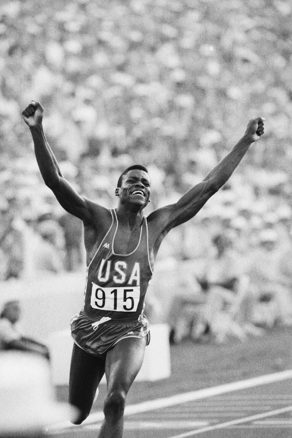 <p>Carl Lewis throws his hands up in victory as he crosses the finish line and wins a gold medal in the men's 100m sprint. The athlete wore a tank top and thigh-grazing athletic shorts for his big win. </p>