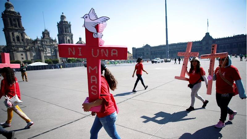 Women carry pink crosses during the protest