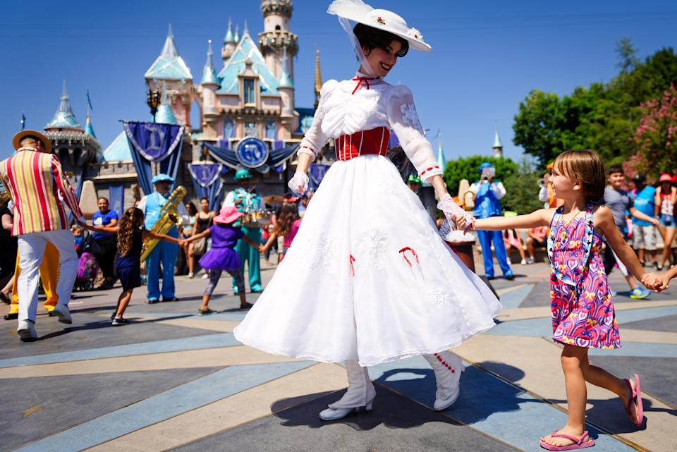 Mary Poppins smiles at a young child as she leads a line of children in song and dance in front of Cinderella's castle during Disney's 60th Diamond Celebration. (Photo: Getty)