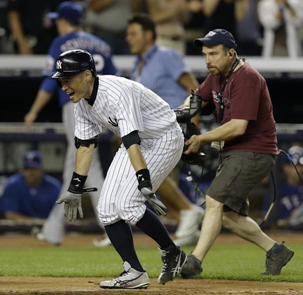 New York Yankees Ichiro Suzuki greets his teammates at the plate after hitting a walk-off solo home against the Texas Rangers in the ninth inning of a baseball game Tuesday, June 25, 2013, in New York. The Yankees won 4-3. (AP Photo/Kathy Willens)