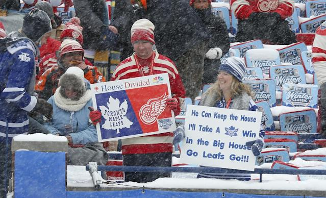 Hockey fans hold up signs during the first period of the Winter Classic outdoor NHL hockey game between the Detroit Red Wings and the Toronto Maple Leafs at Michigan Stadium in Ann Arbor, Mich., Wednesday, Jan. 1, 2014. (AP Photo/Paul Sancya)