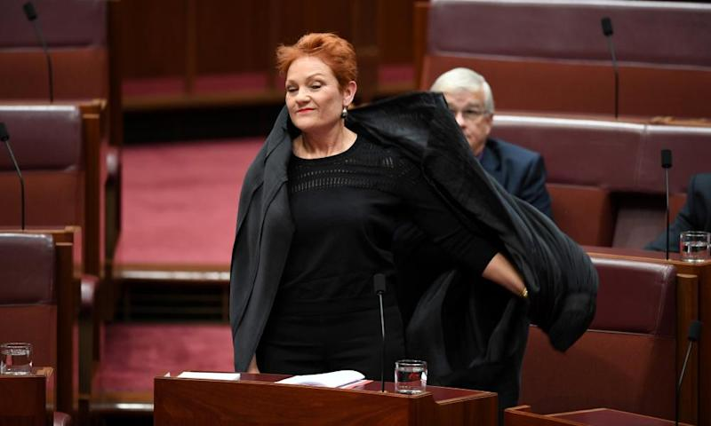 One Nation leader Pauline Hanson pulls off an Islamic veil she wore into the Senate chamber.