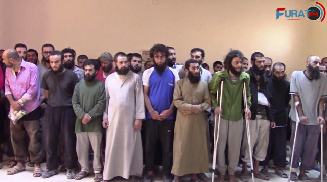 FILE - In this frame grab from a video released In this Oct. 15, 2017, file photo and provided by Furat FM, a Syrian Kurdish activist-run media group, shows Syrian Islamic State group fighters who have surrendered, at a base of the U.S.-backed Syrian Democratic Forces (SDF), in Raqqa, Syria. (Furat FM, via AP, File)