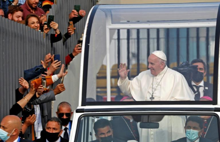 Pope Francis blesses people as he arrives in the popemobile vehicle at the Franso Hariri Stadium