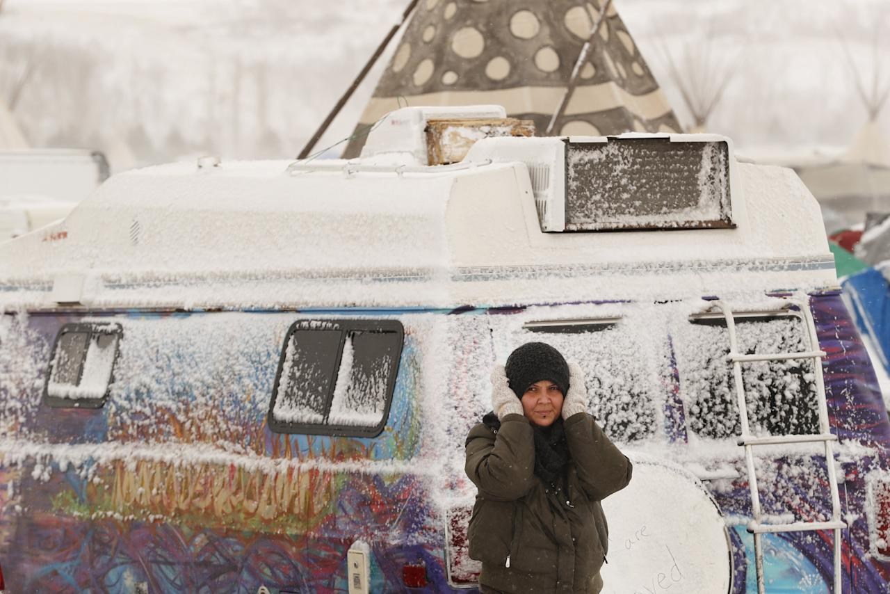 "A camper covers her ears as high winds and a blizzard hit the Oceti Sakowin camp while ""water protectors"" continue to demonstrate against plans to pass the Dakota Access pipeline adjacent to the Standing Rock Indian Reservation, near Cannon Ball, North Dakota, U.S., December 6, 2016.  REUTERS/Lucas Jackson      TPX IMAGES OF THE DAY"
