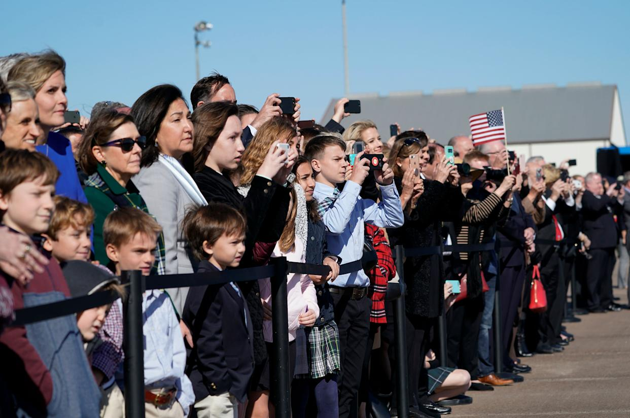 People watch the departure ceremony in Houston.