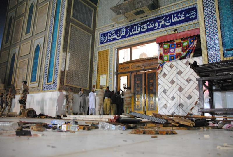Members of the Pakistani bomb disposal team search for evidence at the shrine.