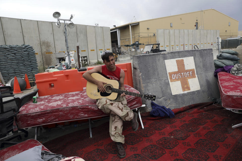 """An Afghan soldier plays a guitar that was left behind after the American military departed Bagram air base, in Parwan province north of Kabul, Afghanistan, Monday, July 5, 2021. The U.S. left Afghanistan's Bagram Airfield after nearly 20 years, winding up its """"forever war,"""" in the night, without notifying the new Afghan commander until more than two hours after they slipped away. (AP Photo/Rahmat Gul)"""