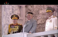"""In this image made from video broadcasted by North Korea's KRT, North Korean leader Kim Jong Un, center, watches military parade during a ceremony to celebrate the 75th anniversary of the country's ruling party in Pyongyang Saturday, Oct. 10, 2020. Kim warned Saturday that his country would """"fully mobilize"""" its nuclear force if threatened as he took center stage at the massive military parade.(KRT via AP)"""