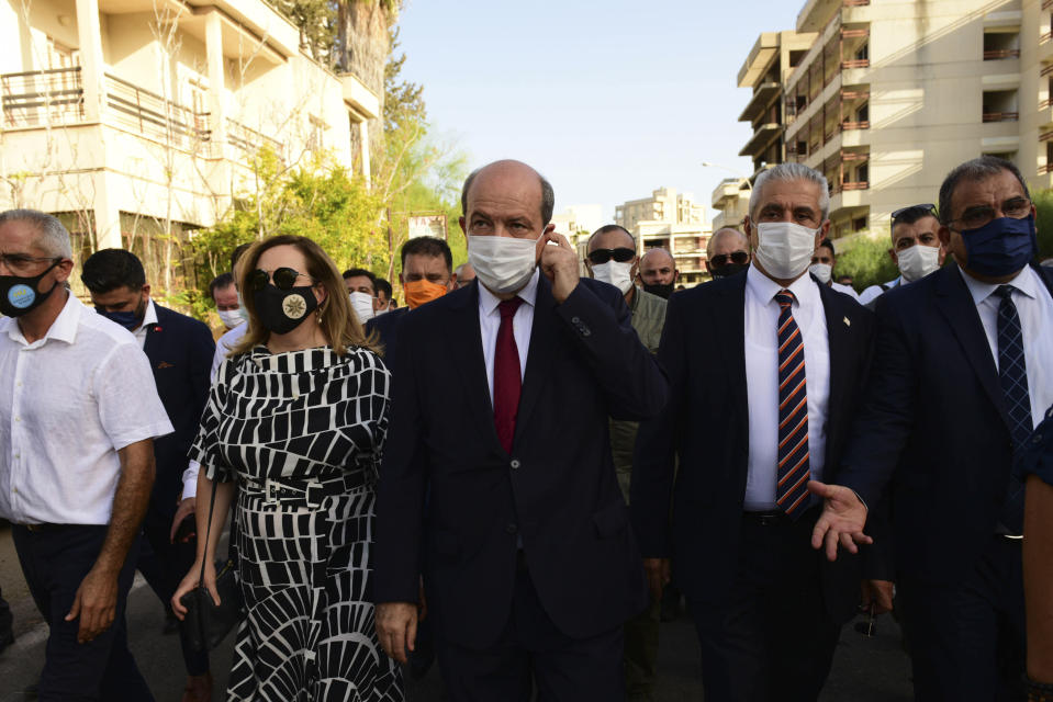 FILE - In this Thursday, Oct. 8, 2020 file photo, Ersin Tatar, center, prime minister of a self-declared Turkish Cypriot state recognized only by Turkey, walks at the abandoned city after police open the beachfront of Varosha, an uninhabited, fenced-off suburb in war-divided Cyprus' in the Turkish occupied area in the breakaway Turkish Cypriot north. Turkish Cypriots will vote Sunday Oct. 11, 2020 to choose a leader who will explore, with rival Greek Cypriots, whether there's enough common ground left for a deal to end the island's decades of ethnic division. (AP Photo/Nedim Enginsoy, File)