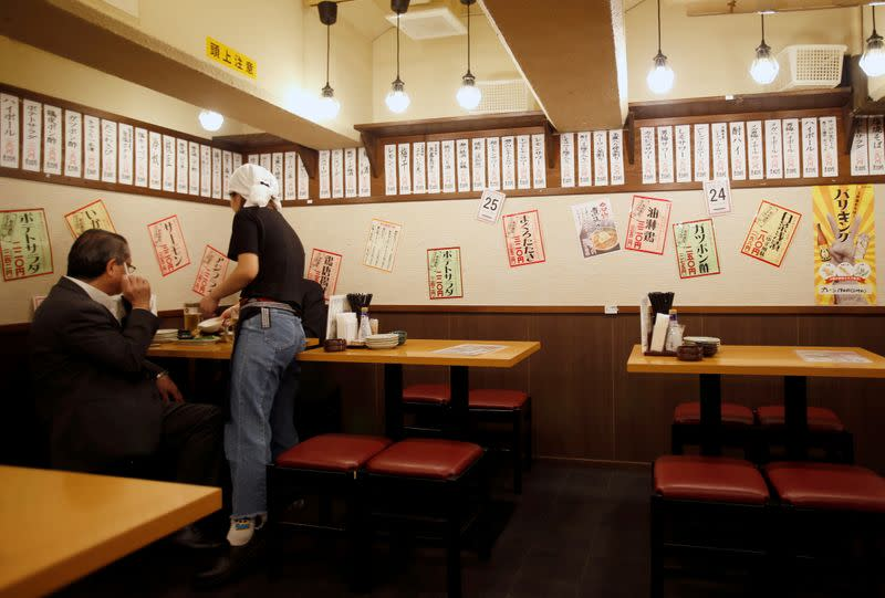 """FILE PHOTO: Office worker is seen at """"Ikken me sakaba"""", a discount izakaya bar offering cheap food and drinks, in Tokyo"""