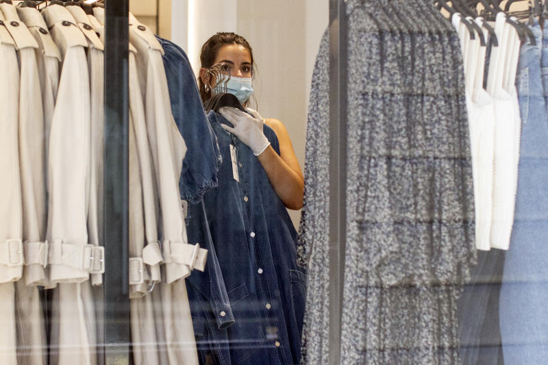 LONDON, ENGLAND - MAY 19: A worker changes clothes rails in a store on Oxford Street on May 19, 2020 in London, England. As shops gear up to open after a long period of closure, clothing stores are beginning to prepare to open their doors, and analysts have suggested that big discounts could be on offer as out of season stock is cleared. The British government has started easing the lockdown it imposed two months ago to curb the spread of Covid-19, abandoning its 'stay at home' slogan in favour of a message to 'be alert', but UK countries have varied in their approaches to relaxing quarantine measures. (Photo by Dan Kitwood/Getty Images)