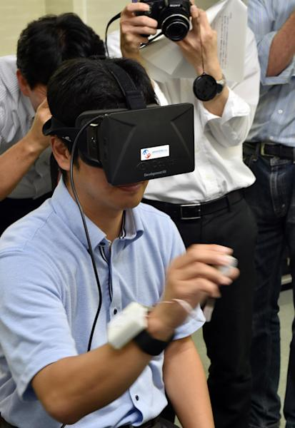 "Japan's high-tech venture Miraisens CEO Natsuo Koda demonstrates ""3D-Haptics technology"", at a press preview in Tsukuba, suburban Tokyo on September 1, 2014 (AFP Photo/Yoshikazu Tsuno)"
