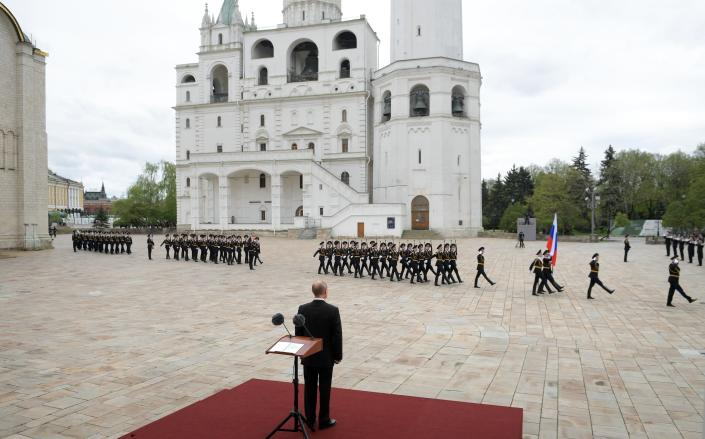 Russian President Vladimir Putin, back to a camera, watches the honour guard of the Presidential Regiment march on Cathedral Square in the Kremlin marking the 75th anniversary of the Nazi defeat in World War II in Moscow, Russia, Saturday, May 9, 2020. Putin cancelled a massive Victory Day marking the 75th anniversary of the Nazi defeat in World War II but ordered a flyby of warplanes over Red Square. (Alexei Druzhinin, Sputnik, Kremlin Pool Photo via AP)