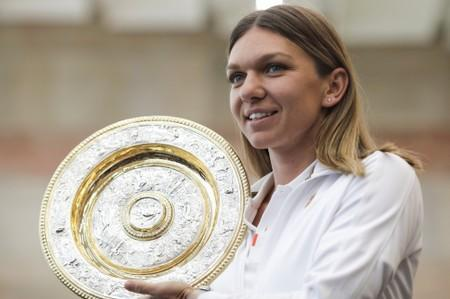 Simona Halep, who became the first Romanian to win a Wimbledon shows her trophy at the airport in Bucharest
