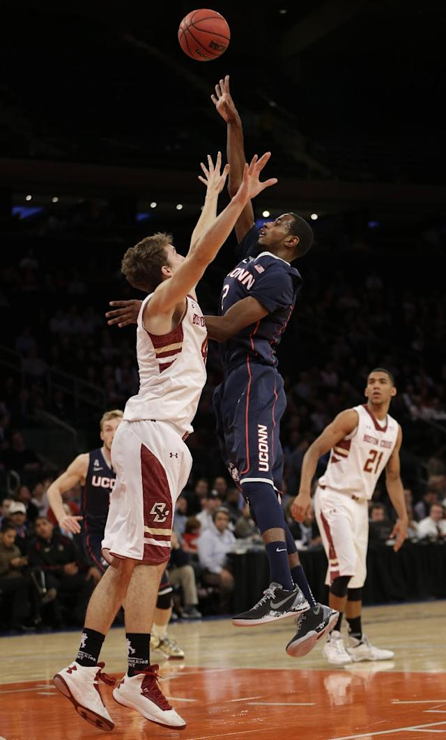 Connecticut's DeAndre Daniels, center, shoots over Boston College's Eddie Odio, left, while Olivier Hanlan looks on during the first half of an NCAA college basketball game Thursday, Nov. 21, 2013, in New York. (AP Photo/Seth Wenig)