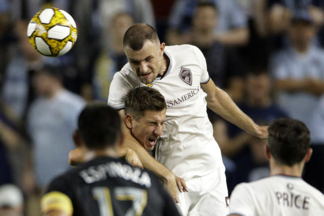 Colorado Rapids defender Tommy Smith, left, and Sporting Kansas City forward Krisztian Nemeth battle for the ball during the first half of an MLS soccer match, Saturday, Sept. 21, 2019, in Kansas City, Kan. (AP Photo/Charlie Riedel)