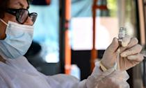 A healthcare worker prepares a dose of vaccine onboard a trolleybus equipped with a vaccination station in Chisinau
