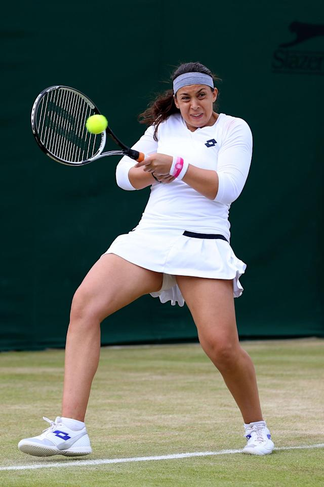 LONDON, ENGLAND - JULY 01: Marion Bartoli of France plays a backhand during her Ladies' Singles fourth round match against Karin Knapp of Italy on day seven of the Wimbledon Lawn Tennis Championships at the All England Lawn Tennis and Croquet Club on July 1, 2013 in London, England. (Photo by Julian Finney/Getty Images)