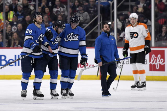 Winnipeg Jets' Mathieu Perreault (85) is helped off the ice by teammates Nathan Beaulieu (88) and Andrew Copp (9) after being injured during second-period NHL hockey game action against the Philadelphia Flyers in Winnipeg, Manitoba, Sunday, Dec. 15, 2019. (Fred Greenslade/The Canadian Press via AP)