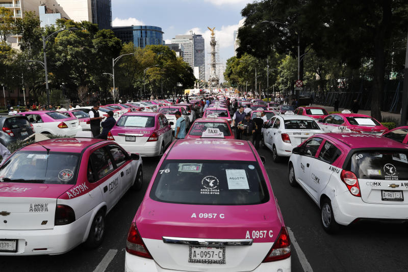 Hundreds of taxi drivers gather round the Angel of Independence monument to protest ride apps, in Mexico City, Monday, Oct. 7, 2019. The protesters want the apps banned, arguing that the apps are unfair competition because those drivers are more loosely regulated and don't have to pay licensing fees. (AP Photo/Marco Ugarte)