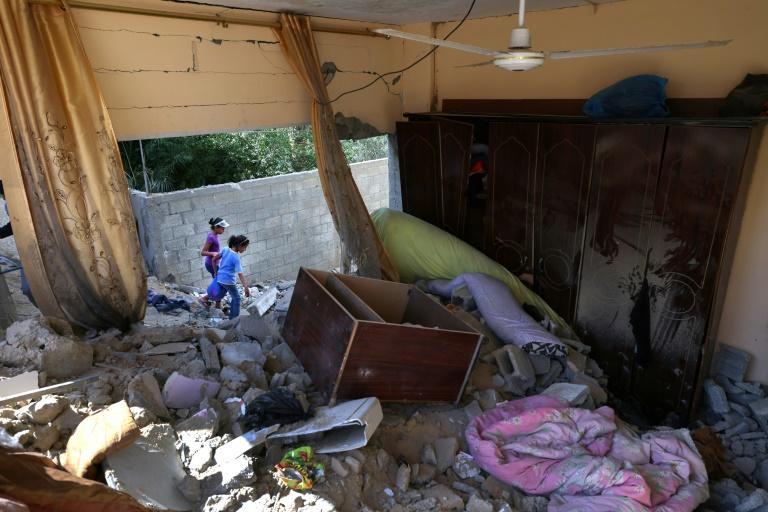 Palestinian children walk amidst the rubble of buildings destroyed by Israeli strikes in the northern Gaza Strip