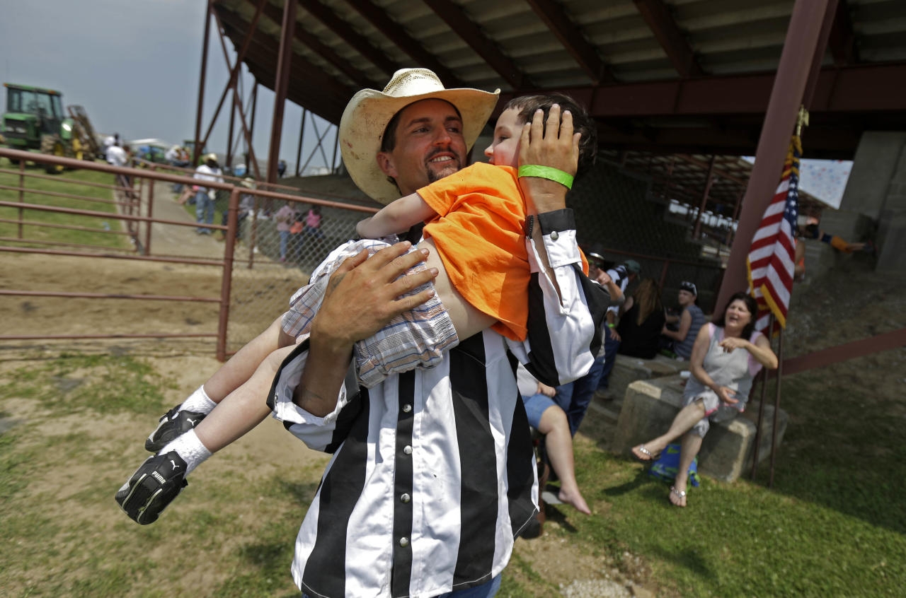 "Inmate Joseph Ward plays with his nephew Eric Young, 3, who he has not seen since he was an infant, before the start of the Angola Prison Rodeo in Angola, La., Saturday, April 26, 2014. Louisiana's most violent criminals, many serving life sentences for murder, are the stars of the Angola Prison Rodeo, the nation's longest-running prison rodeo that this year celebrates 50 years. The event has grown from a small ""fun"" event for prisoners into big business, with proceeds going into the Louisiana State Penitentiary Inmate Welfare Fund for inmate education and recreational supplies. (AP Photo/Gerald Herbert)"