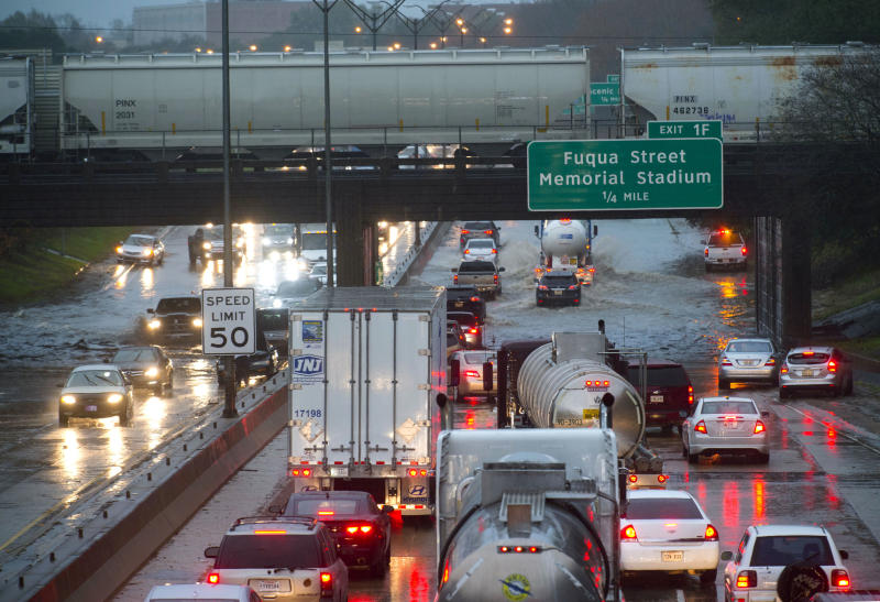 Cars stack up northbound on Interstate 110, as they encounter high water in the roadway under the railroad bridge near the governor's mansion, as even fewer vehicles opt to try to navigate the water as they progress southbound after heavy rains, Thursday, Dec. 27, 2018, in Baton Rouge, La. (Travis Spradling/The Advocate via AP)