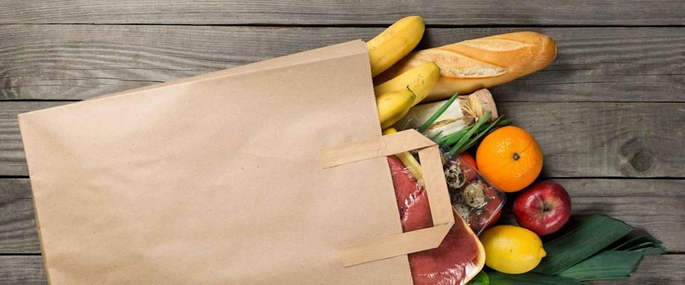 Different food in paper bag on wooden background, close up.