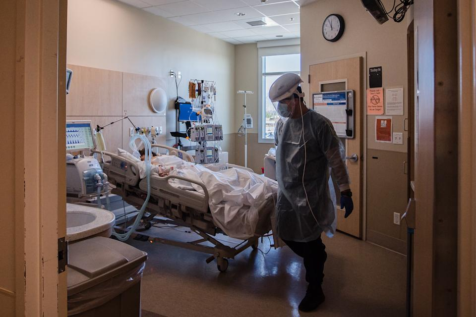 A Healthcare worker checks on a patient in the Covid-19 Intensive Care Unit (ICU) overflow area at Providence Holy Cross Medical Center in Mission Hills, California, U.S., on Friday, Feb. 5, 2021. (Ariana Drehsler/Bloomberg via Getty Images)