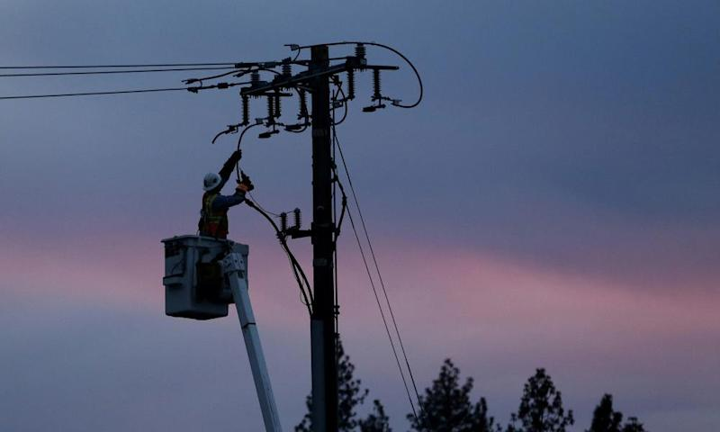 A Pacific Gas and Electric lineman works to repair a power line in fire-ravaged Paradise, California, in 2018.
