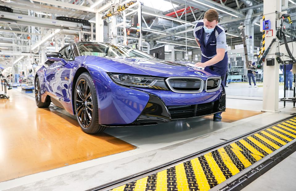 11 June 2020, Saxony, Leipzig: The last BMW i8 is at the end of the One employee wipes the last BMW i8 with a cloth at the end of the production line. Six years after its market launch, the last plug-in hybrid sports car has rolled off the production line here. A total of 20 488 of these cars were produced at the Leipzig plant. This makes the hybrid sports car with electric and gasoline engines by far the best-selling sports car at BMW. The vehicle with a passenger cell made of carbon-reinforced plastic (CFRP) won numerous awards. In addition to vehicles with combustion engines, BMW also builds the electric model i3 in Leipzig. Photo: Jan Woitas/dpa-Zentralbild/ZB (Photo by Jan Woitas/picture alliance via Getty Images)