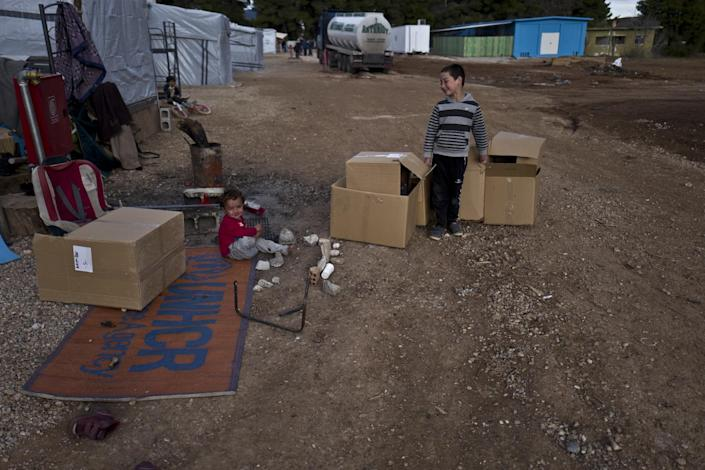 A Syrian refugee child plays on the ground while a boy collects cardboard boxes at the refugee camp of Ritsona about 86 kilometers (53 miles) north of Athens, Thursday, Jan. 5, 2017. Over 62,000 refugees and migrants are stranded in Greece after a series of Balkan border closures and an European Union deal with Turkey to stop migrant flows. (AP Photo/Muhammed Muheisen)