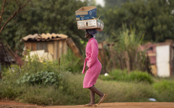 A woman carrying boxes on her head at a informal settlement, east of Johannesburg, South Africa, Friday, March 27, 2020. (AP Photo/Themba Hadebe)