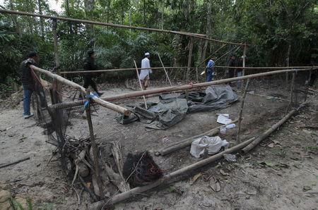 Security forces and rescue workers inspect an abandoned camp at a rubber plantation near a mountain in Thailand's southern Songkhla province May 7, 2015. REUTERS/Surapan Boonthanom