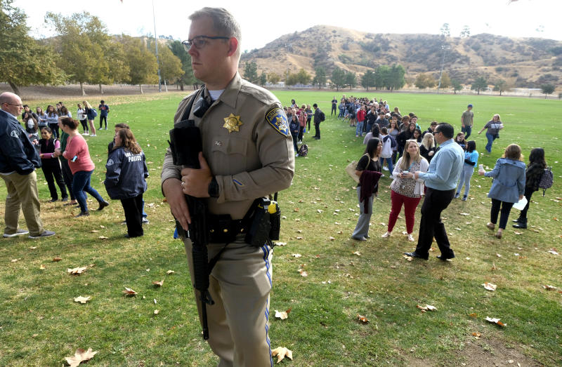 A police officer stands guard as students wait to reunite with their parents following a shooting at Saugus High School that injured several people, Nov. 14, 2019, in Santa Clarita, Calif. (Photo: Ringo H.W. Chiu/AP)