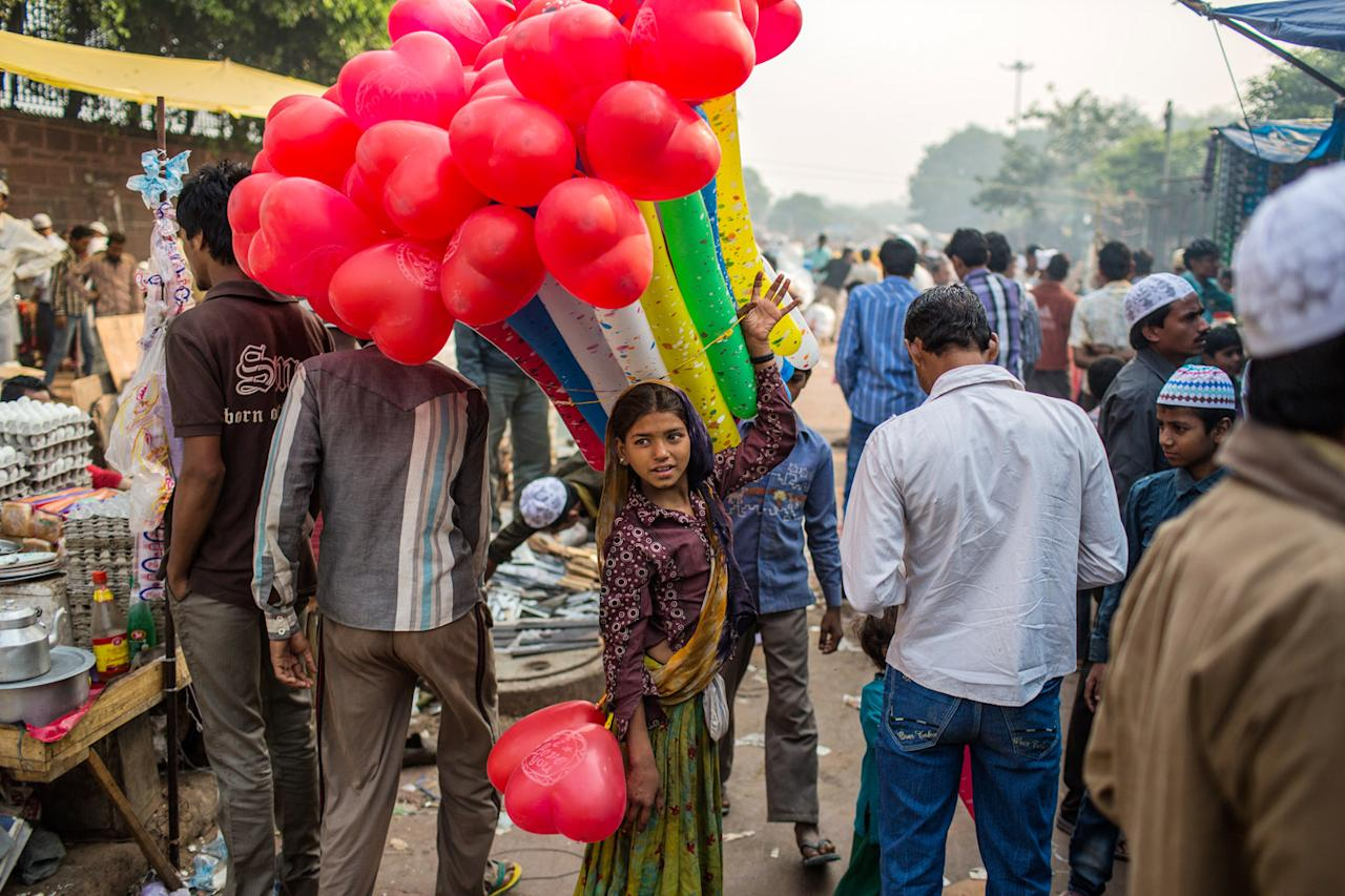 A girl selling balloons looks on after  Eid al-Adha prayers outside of the Jama Masjid on October 27, 2012 in New Delhi, India. Eid al-Adha, also known as the Feast of Sacrifice, commemorates Abraham's willingness to sacrifice his son as an act of obedience to God, who in accordance with tradition then provided a lamb in the boy's place. (Photo by Daniel Berehulak/Getty Images)