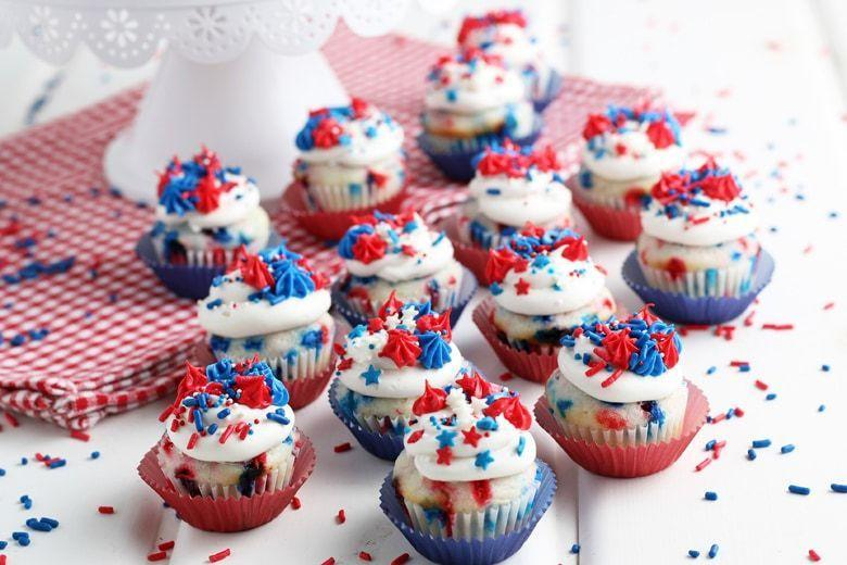 """<p>These mini cupcakes get a double dose of red, white, and blue: There are sprinkles in the cake batter <em>and</em> on top!</p><p><strong>Get the recipe at <a href=""""https://www.savoryexperiments.com/4th-of-july-cupcakes/"""" rel=""""nofollow noopener"""" target=""""_blank"""" data-ylk=""""slk:Savory Experiments"""" class=""""link rapid-noclick-resp"""">Savory Experiments</a>.</strong><br><br><a class=""""link rapid-noclick-resp"""" href=""""https://go.redirectingat.com?id=74968X1596630&url=https%3A%2F%2Fwww.walmart.com%2Fsearch%2F%3Fquery%3Dmini%2Bcupcake%2Bpan%26typeahead%3DMINI%2BCUP&sref=https%3A%2F%2Fwww.thepioneerwoman.com%2Ffood-cooking%2Frecipes%2Fg36343624%2F4th-of-july-cupcakes%2F"""" rel=""""nofollow noopener"""" target=""""_blank"""" data-ylk=""""slk:SHOP MINI CUPCAKE PANS"""">SHOP MINI CUPCAKE PANS</a></p>"""