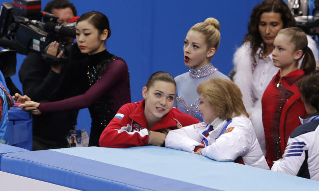 Adelina Sotnikova of Russia, centre, speaks with her coach Elena Buianova, centre right, before competing in the women's free skate figure skating finals at the Iceberg Skating Palace during the 2014 Winter Olympics, Thursday, Feb. 20, 2014, in Sochi, Russia. Visible at back left is Yuna Kim of South Korea, in centre back Gracie Gold of the United States and at back right Julia Lipnitskaya of Russia. (AP Photo/Darron Cummings)