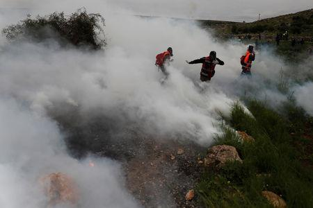 Medics run away from tear during clashes between Palestinians and Israeli troops at a protest marking the Land Day, in al-Mughayer village in the Israeli-occupied West Bank March 29, 2019. REUTERS/Mohamad Torokman
