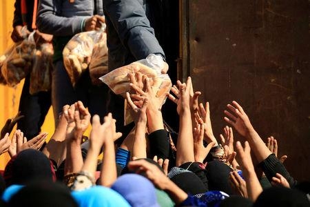 Displaced Iraqi people who fled from homes during a battle between Iraqi forces and Islamic State militants, receive bread at the Hammam al-Alil camp, south of Mosul