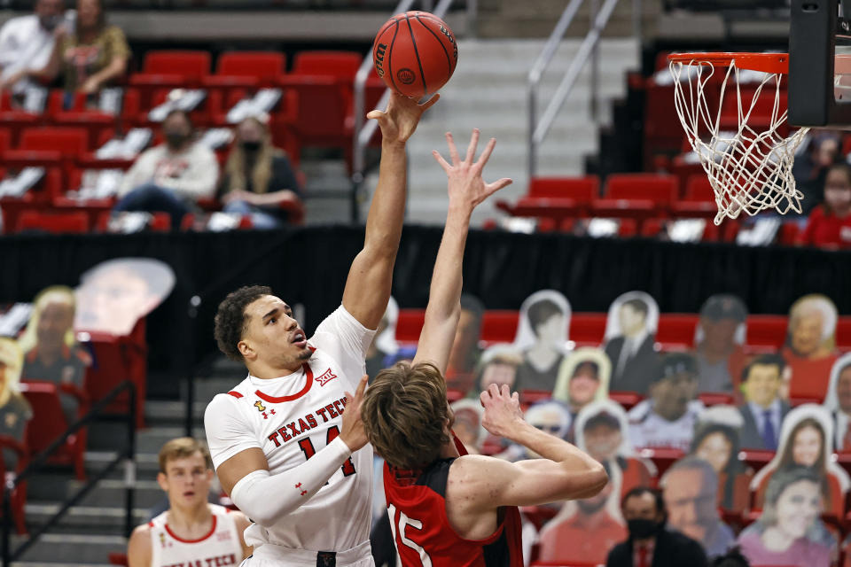 Texas Tech's Marcus Santos-Silva (14) shoots over Incarnate Word's Marcus Larsson (15) during the first half of an NCAA college basketball game Tuesday, Dec. 29, 2020, in Lubbock, Texas. (AP Photo/Brad Tollefson)