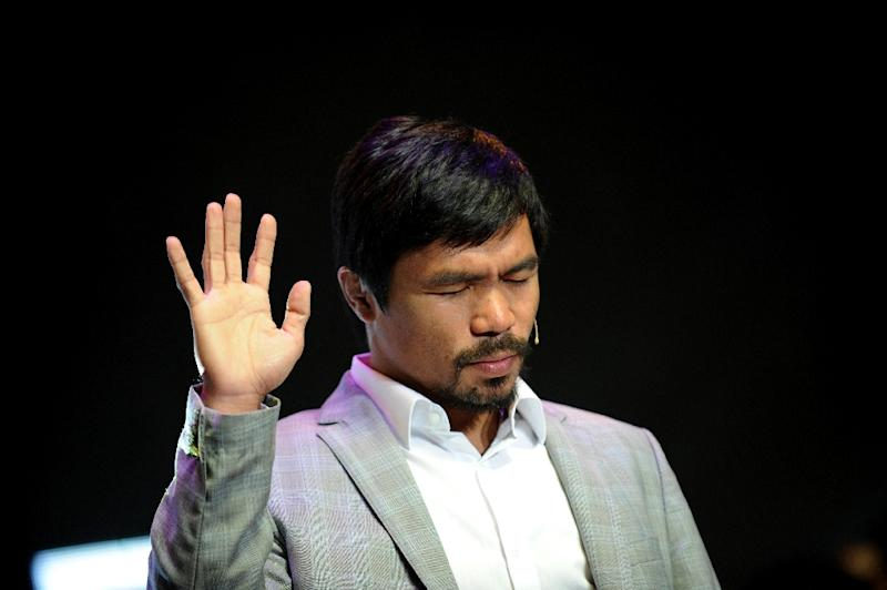 Philippine boxing icon Manny Pacquiao gestures during a prayer rally at the Araneta Coliseum in Manila on July 28, 2012 (AFP Photo/Noel Celis)