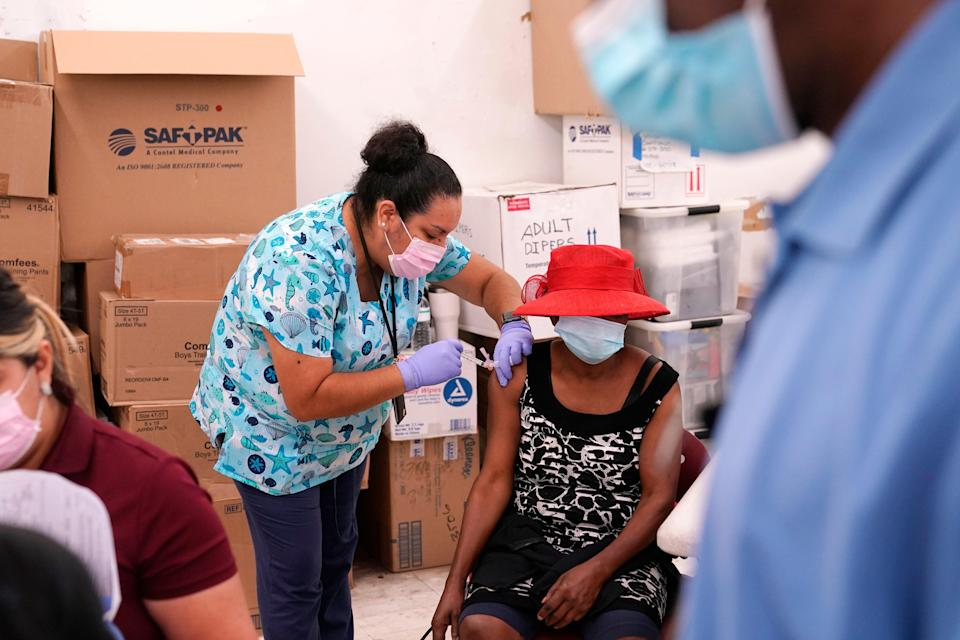 Registered nurse Ashleigh Velasco, left, administers the Johnson & Johnson COVID-19 vaccine to Rosemene Lordeus, right, at a clinic held by Healthcare Network in Immokalee, Fla (AP)