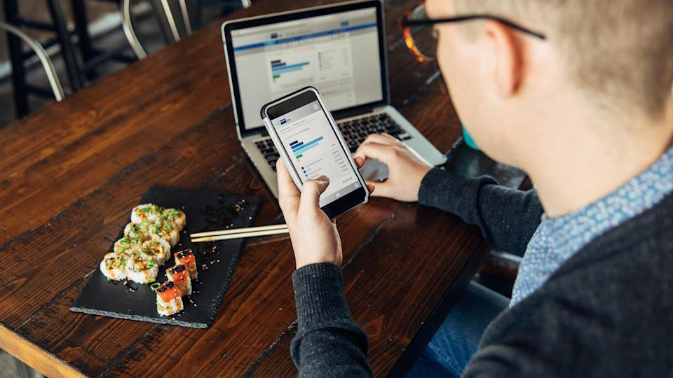 A man of the Millennial Generation is looking at his financial statement while eating lunch at a local sushi restaurant.