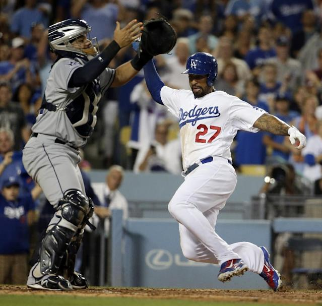 Los Angeles Dodgers' Matt Kemp, right, scores past San Diego Padres catcher Rene Rivera on Justin Turner's his RBI-double during fourth inning of a baseball game in Los Angeles, Tuesday, Aug. 19, 2014. (AP Photo/Chris Carlson)