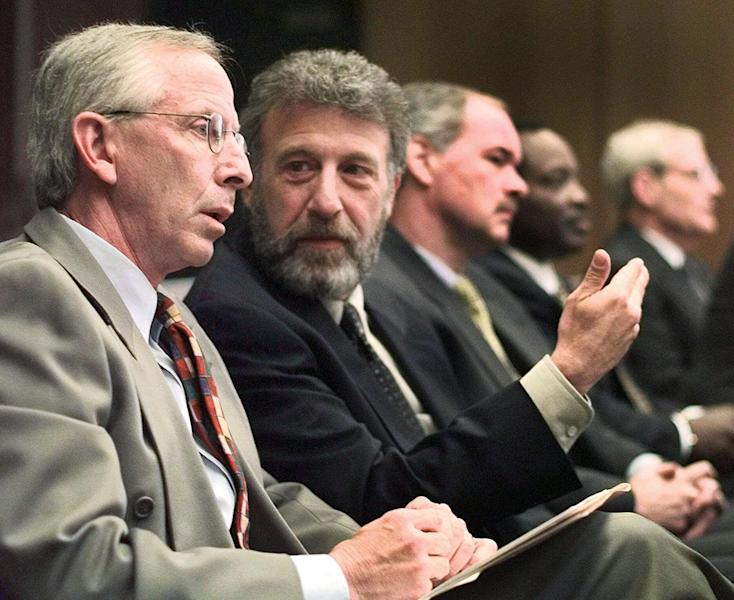 <p> FILE - In this Thursday, May 6, 1999 file photo, George Zimmer, second from left, gestures to Andy Dolich prior to a meeting, in Oakland, Calif. Men's Wearhouse Inc. says it has dismissed Zimmer, its founder and executive chairman. In a terse release issued Wednesday, June 19, 2013, the company didn't give a reason for the abrupt firing of Zimmer, who built Men's Wearhouse from one small Texas store using a cigar box as a cash register to one of the nation's largest specialty retailers in men's clothing, with 1,143 locations. (AP Photo/Ben Margot, File)