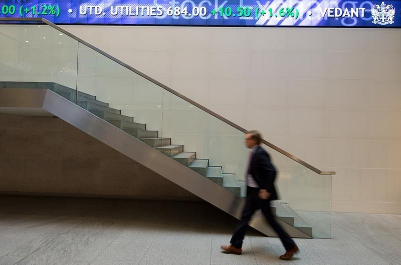 A man walks under an electronic information board at the London Stock Exchange in the City of London