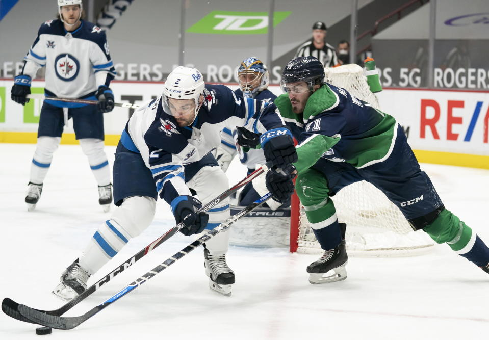 Vancouver Canucks center Zack MacEwen (71) fights for control of the puck with Winnipeg Jets defenseman Dylan DeMelo (2) during second-period NHL hockey game action in Vancouver, British Columbia, Sunday, Feb. 21, 2021. (Jonathan Hayward/The Canadian Press via AP)
