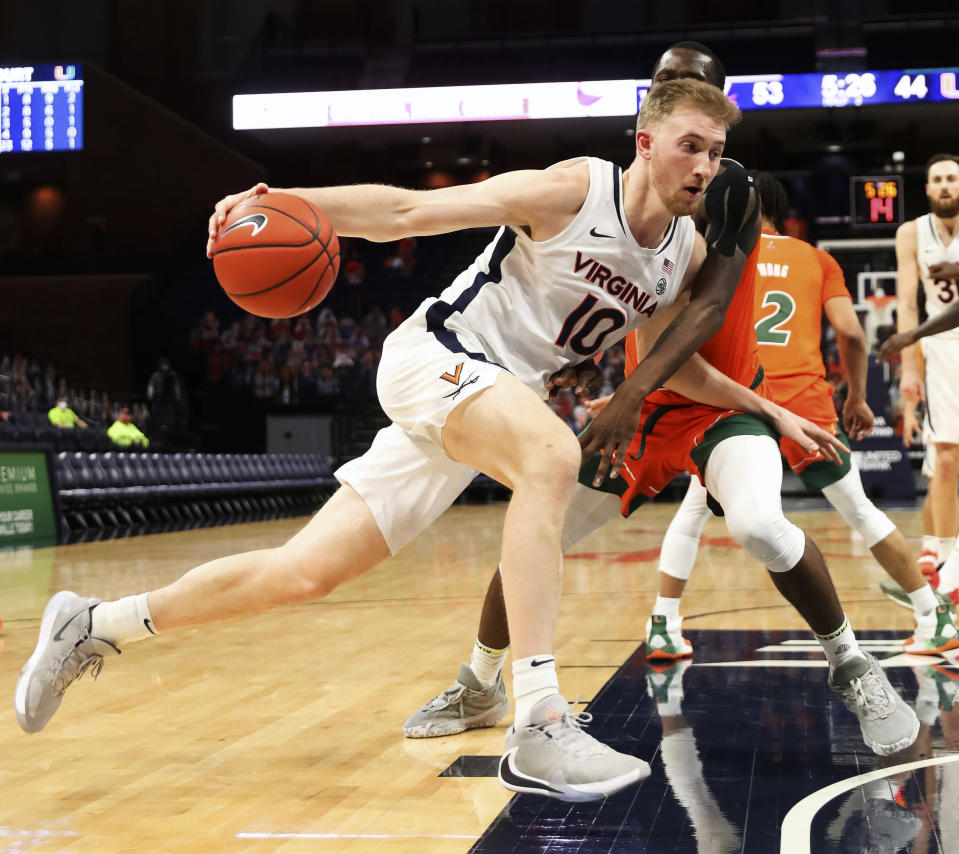 Virginia forward Sam Hauser (10) drives past Miami guard Elijah Olaniyi (4) during an NCAA college basketball game, Monday, March 1, 2021, in Charlottesville, Va. (Andrew Shurtleff/The Daily Progress via AP, Pool)